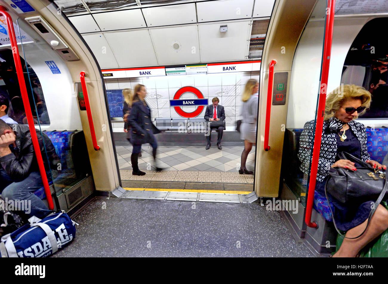 London, England, UK. London Underground tube station: train doors open at Bank station - businessman on the platform - Stock Image