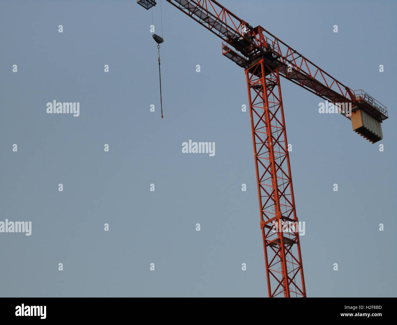 an artsy shot of an orange crane against a clear blue sky, detail - Stock Image