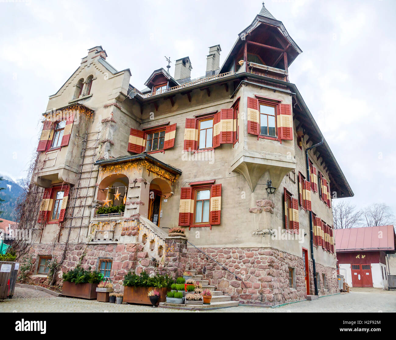 Brunico, Italy, 14 December 2014: a strange and imposing big house with colorful vivid red windows during the christmas - Stock Image