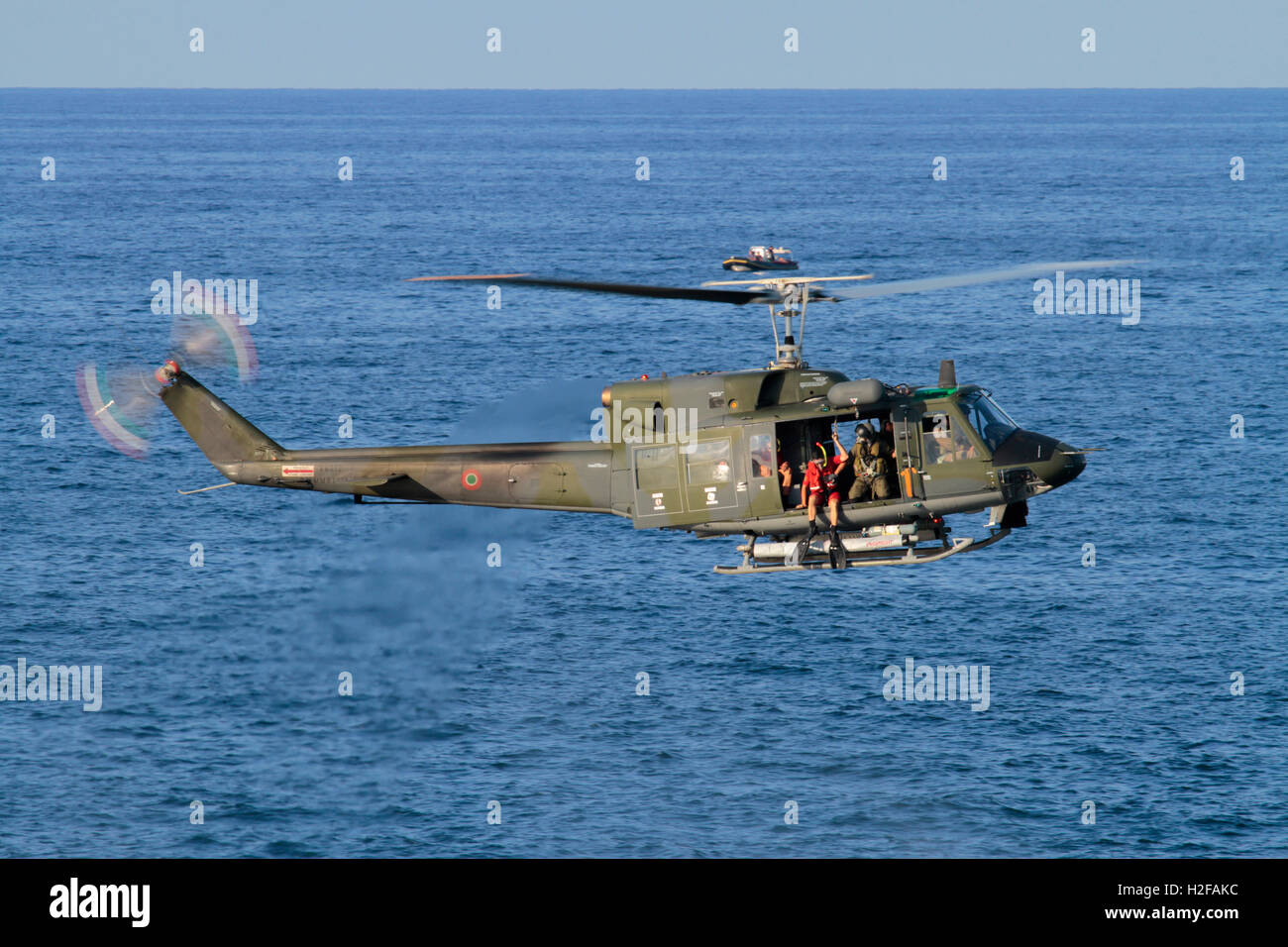 Diver preparing to jump from an Italian Air Force or Aeronautica Militare Italiana Agusta-Bell AB212 helicopter - Stock Image
