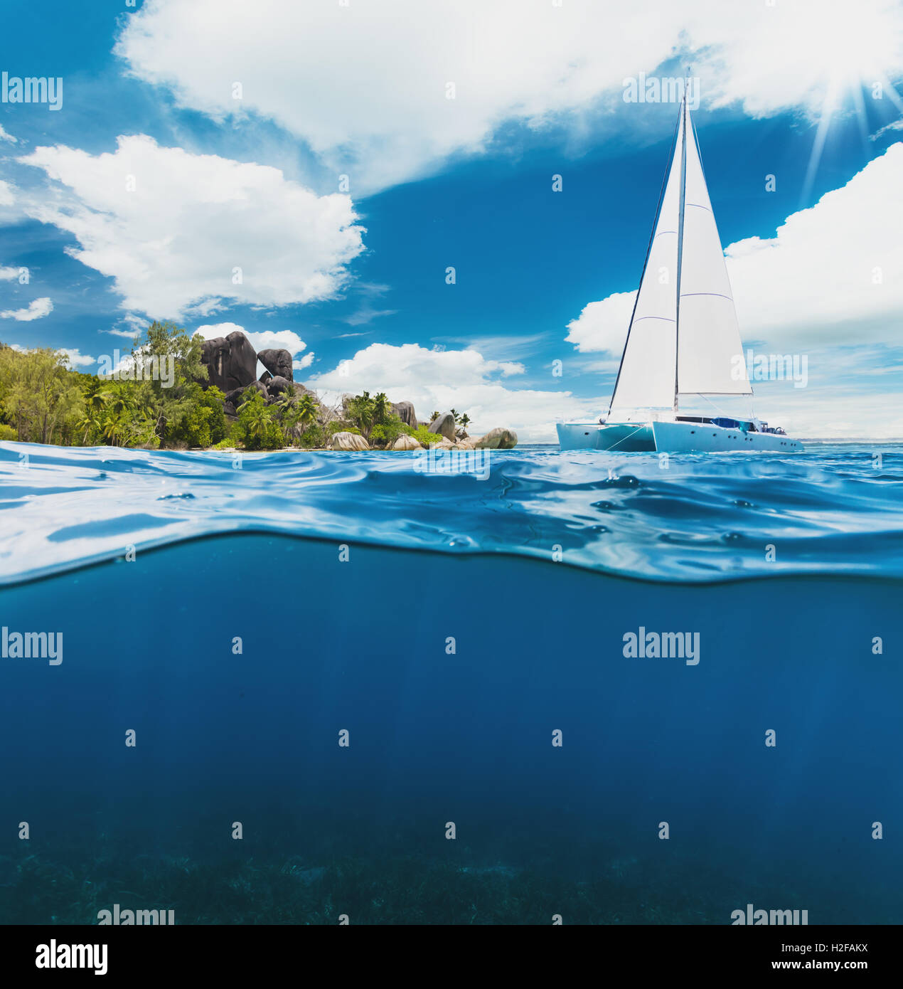 Catamaran boat sailing next to tropical island in Seychelles Stock Photo