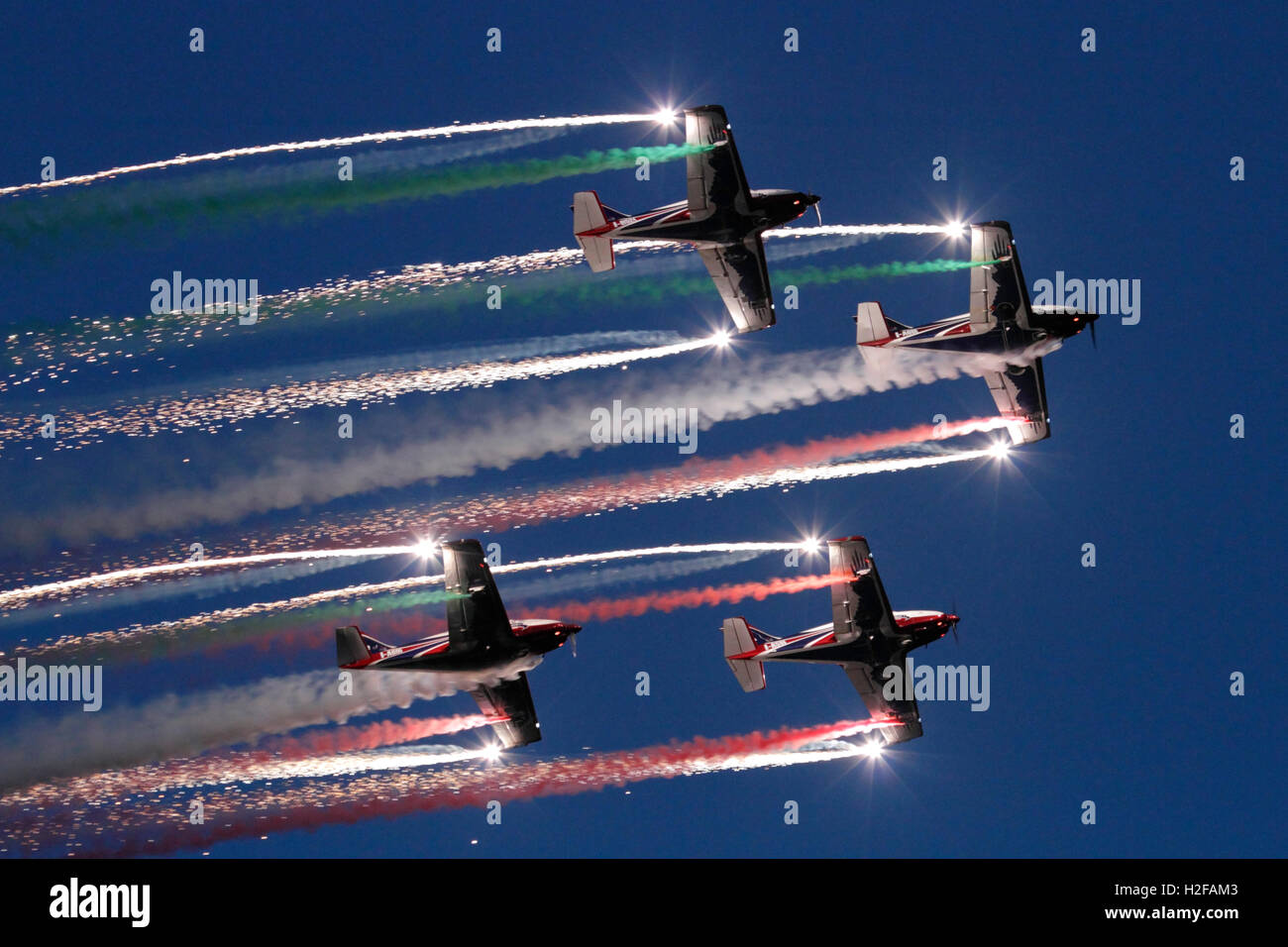 The Pioneer Team flying their Alpi Aviation Pioneer 300 aircraft in a spectacular airshow display at dusk - Stock Image