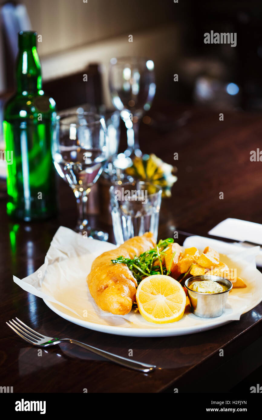 Village public house food. A cooked main course, dish on  a dining table, fish and chips. Glass of water and a green - Stock Image