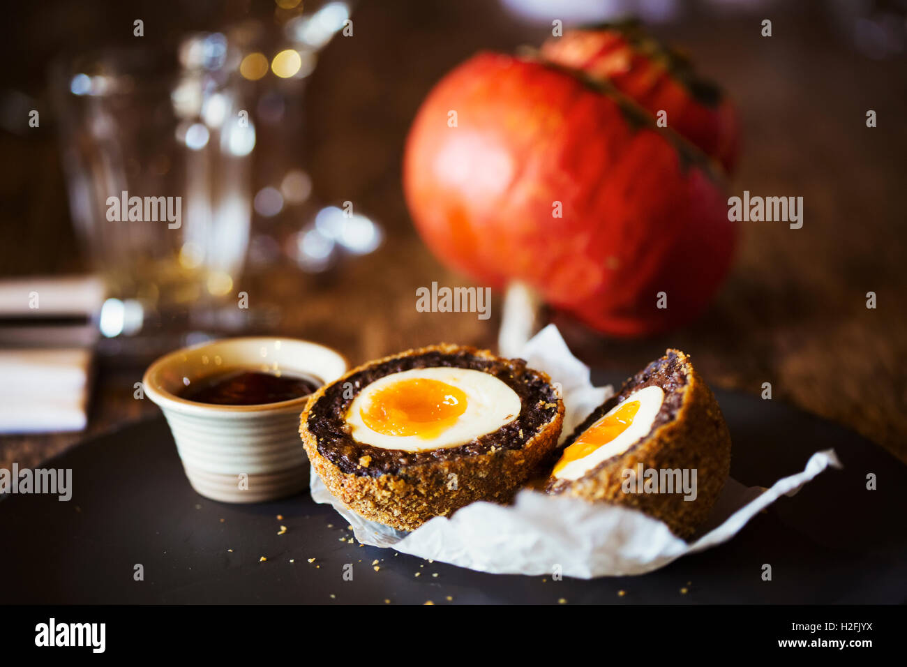 Village public house food. A dish with a fresh made scotch egg cut in to two and a pot of sauce. - Stock Image