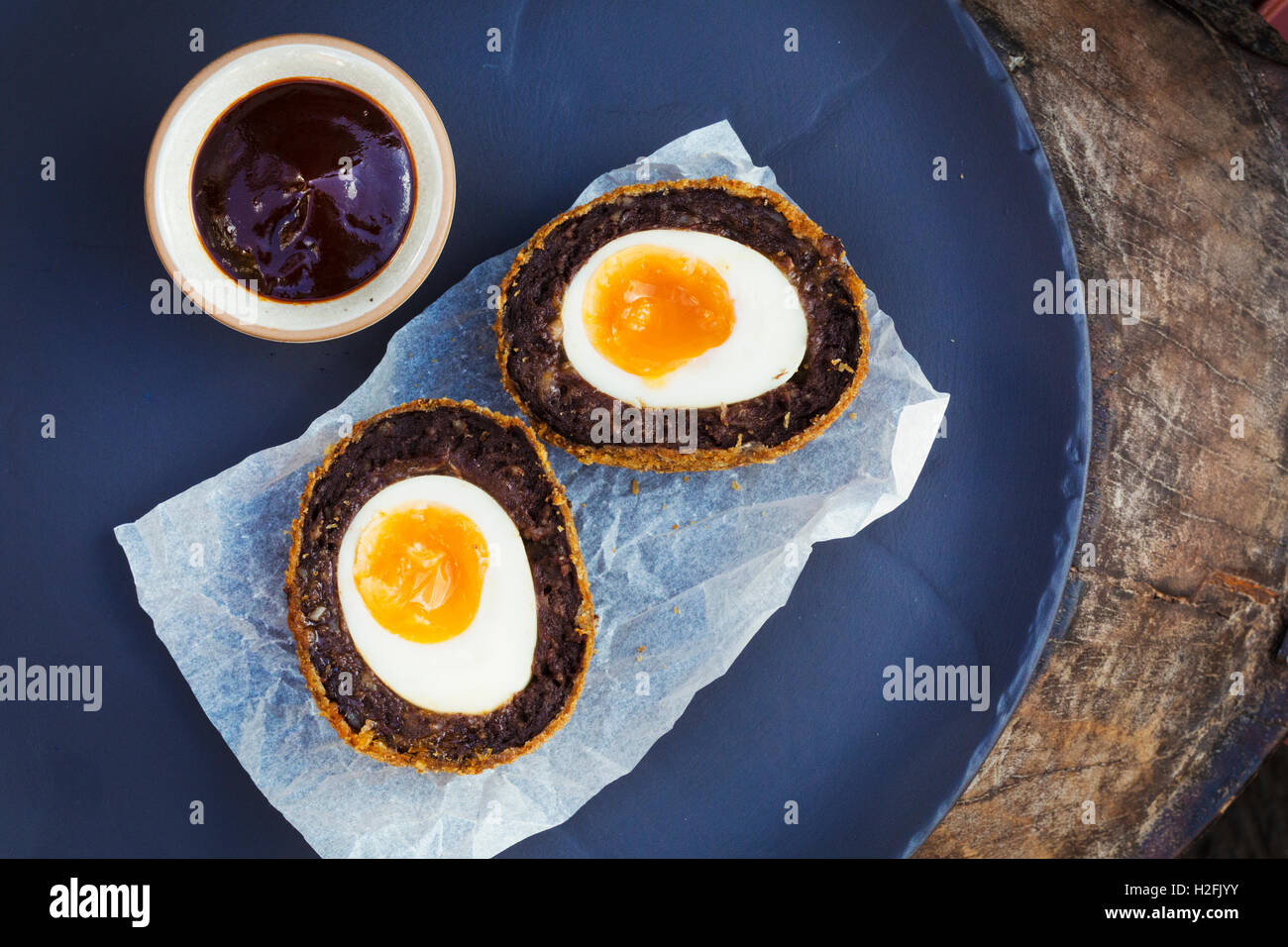 Village pub food. A blue dish with a fresh made scotch egg cut in to two and a pot of sauce. - Stock Image