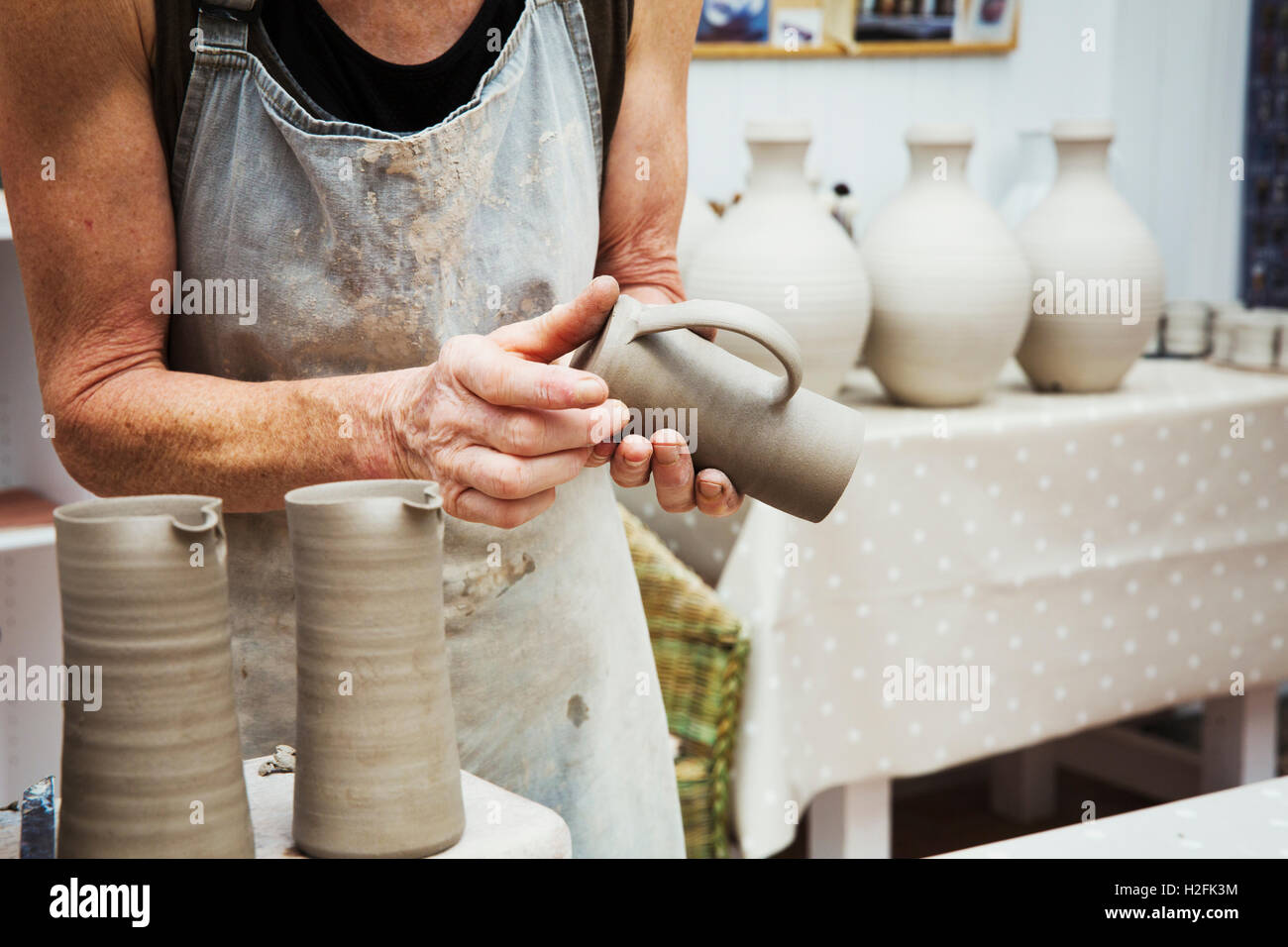 A potter handling a wet clay pot, smoothing the bottom and preparing it for kiln firing. Stock Photo