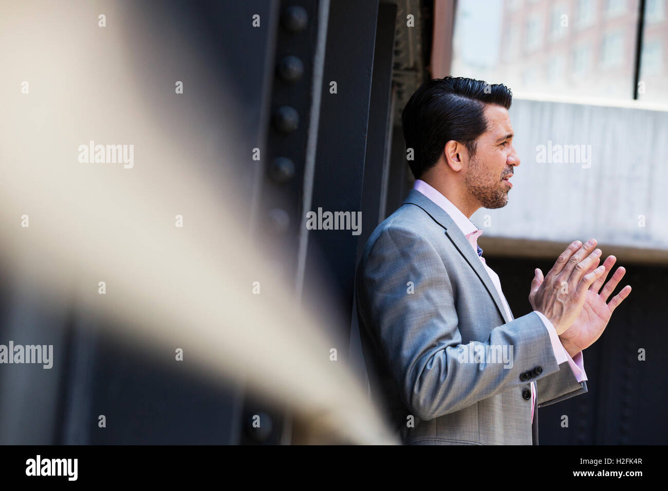 Businessman wearing a grey suit standing outdoors, talking and gesturing with his hands raised. - Stock Image