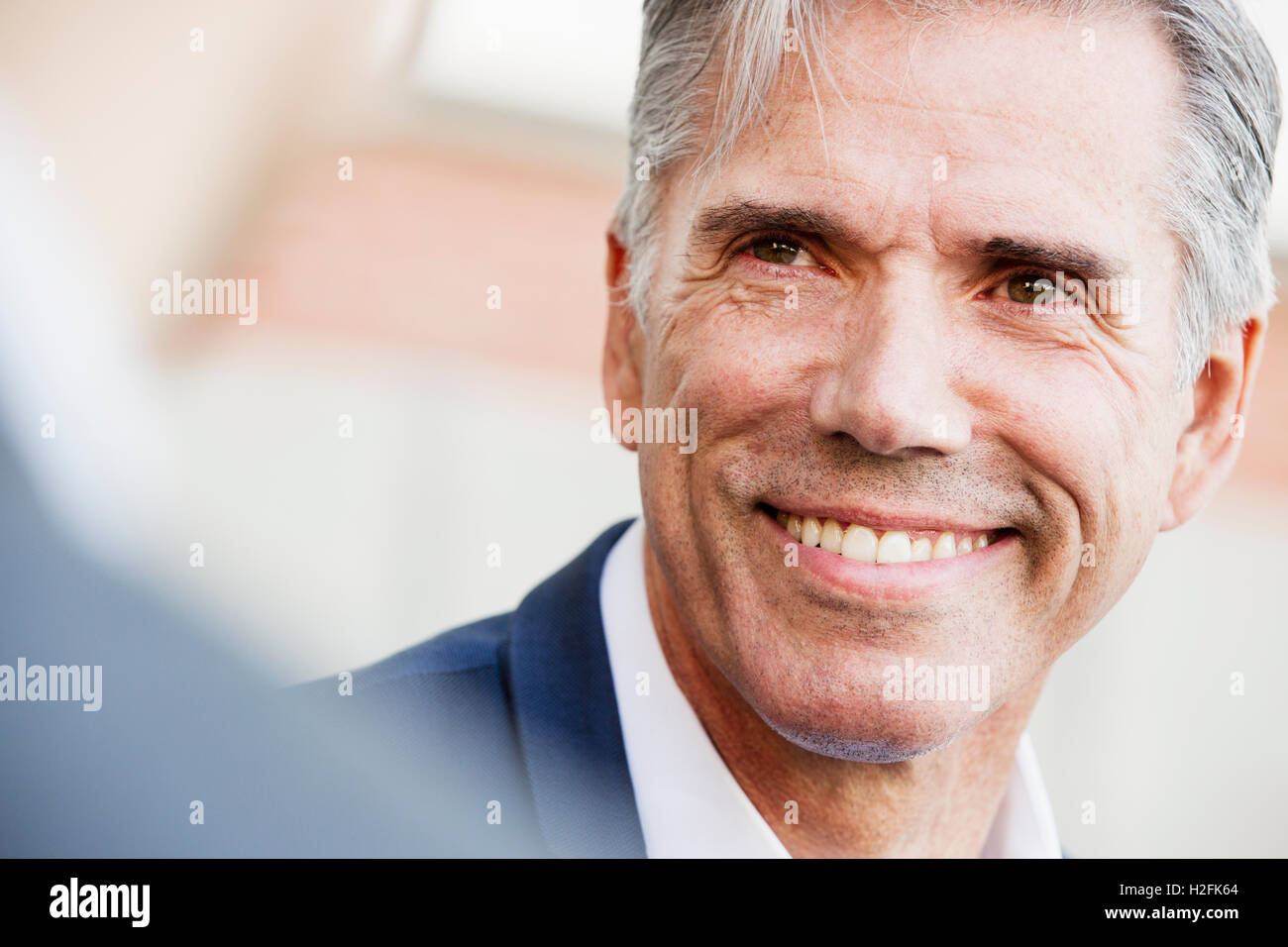 A man in a white shirt with grey hair, smiling, his head turned to speak to another person . - Stock Image