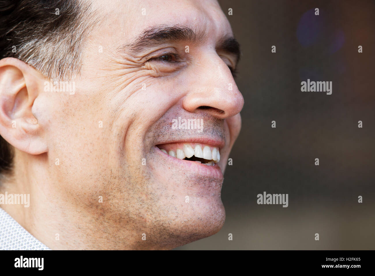 A man with greying hair in a shirt, looking sideways, smiling. - Stock Image