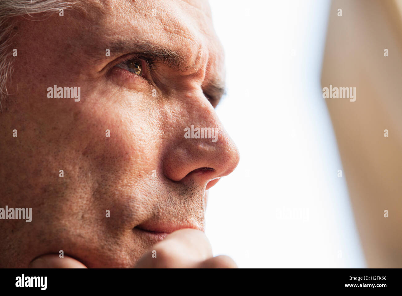 Close up of a man's face, his hand on  his chin, looking into the distance. - Stock Image