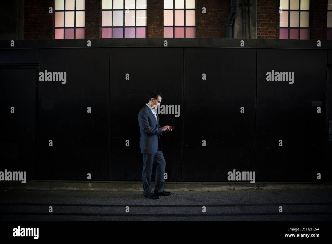 A man in a suit standing in shadow on  a city street under a lit window, checking his phone. - Stock Image