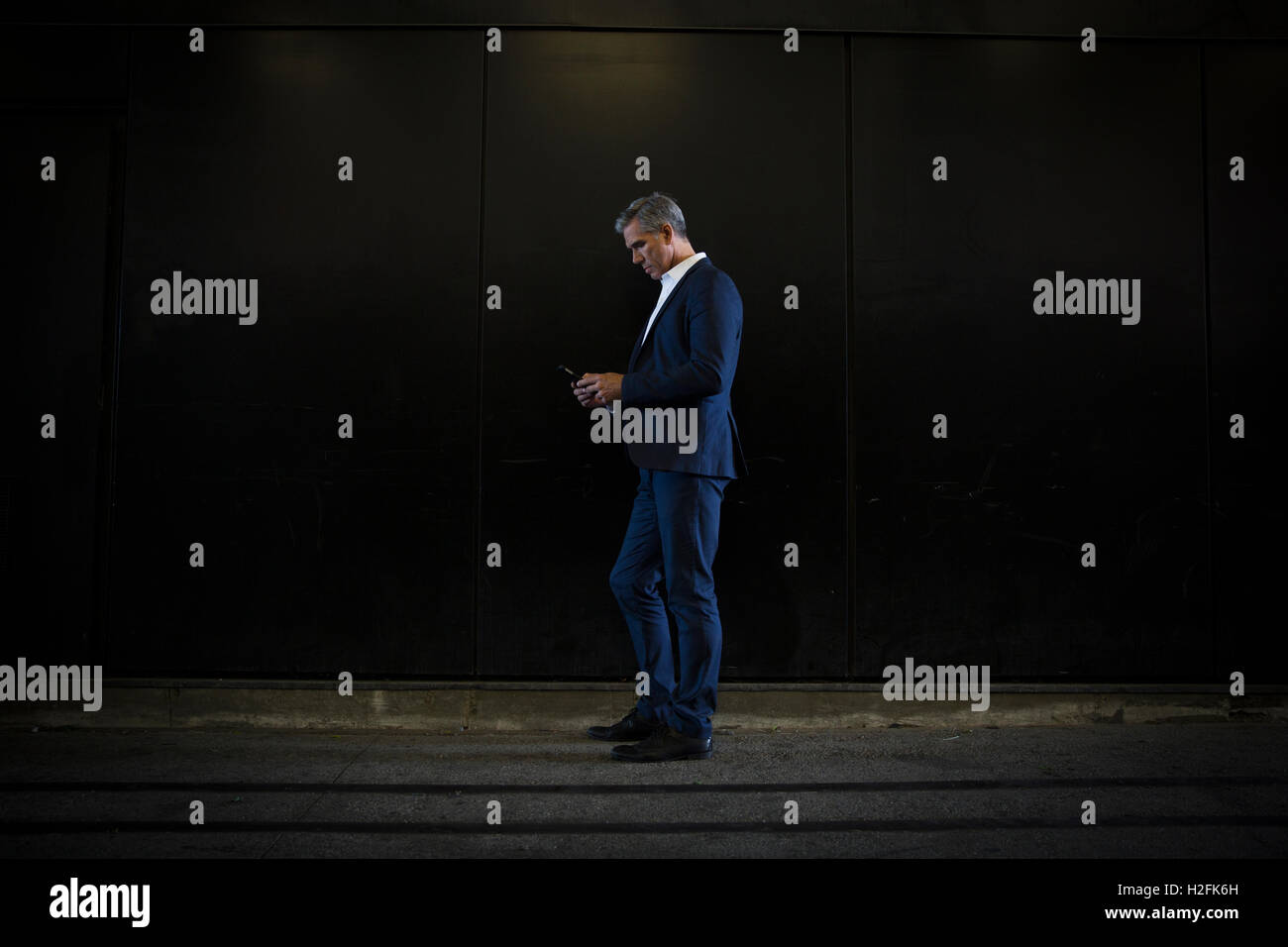 A man in a suit standing in shadow on  a city street, looking at his smart phone, texting - Stock Image