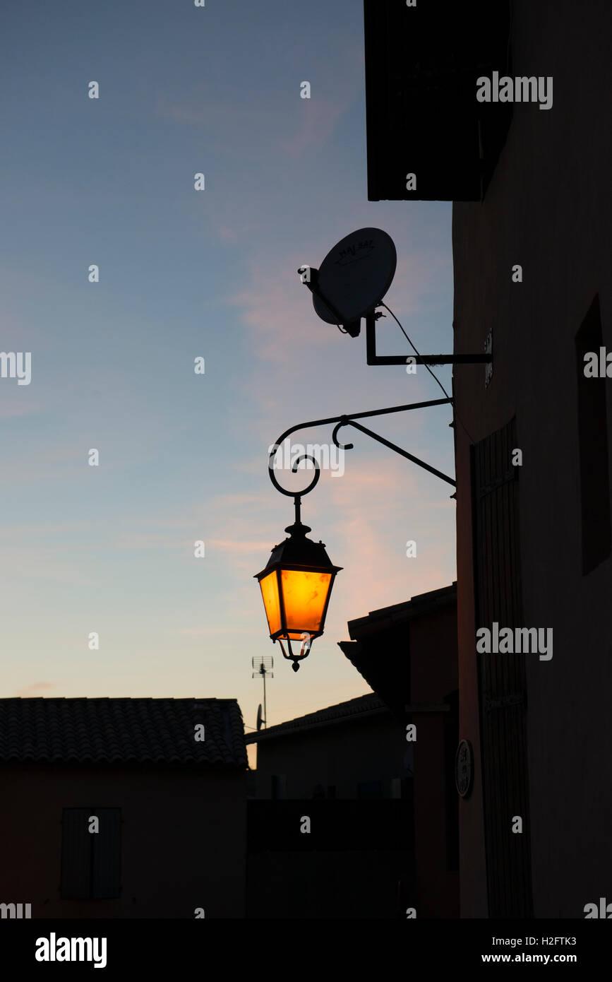 Shining street lantern at dusk, St. Gilles, Gard department, southern France - Stock Image