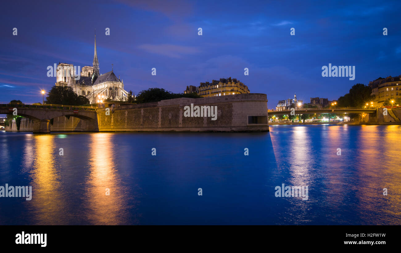 The iconic gothic Cathedral Notre Dame De Paris and the River Seine seen from the Quai de la Tournelle at night - Stock Image