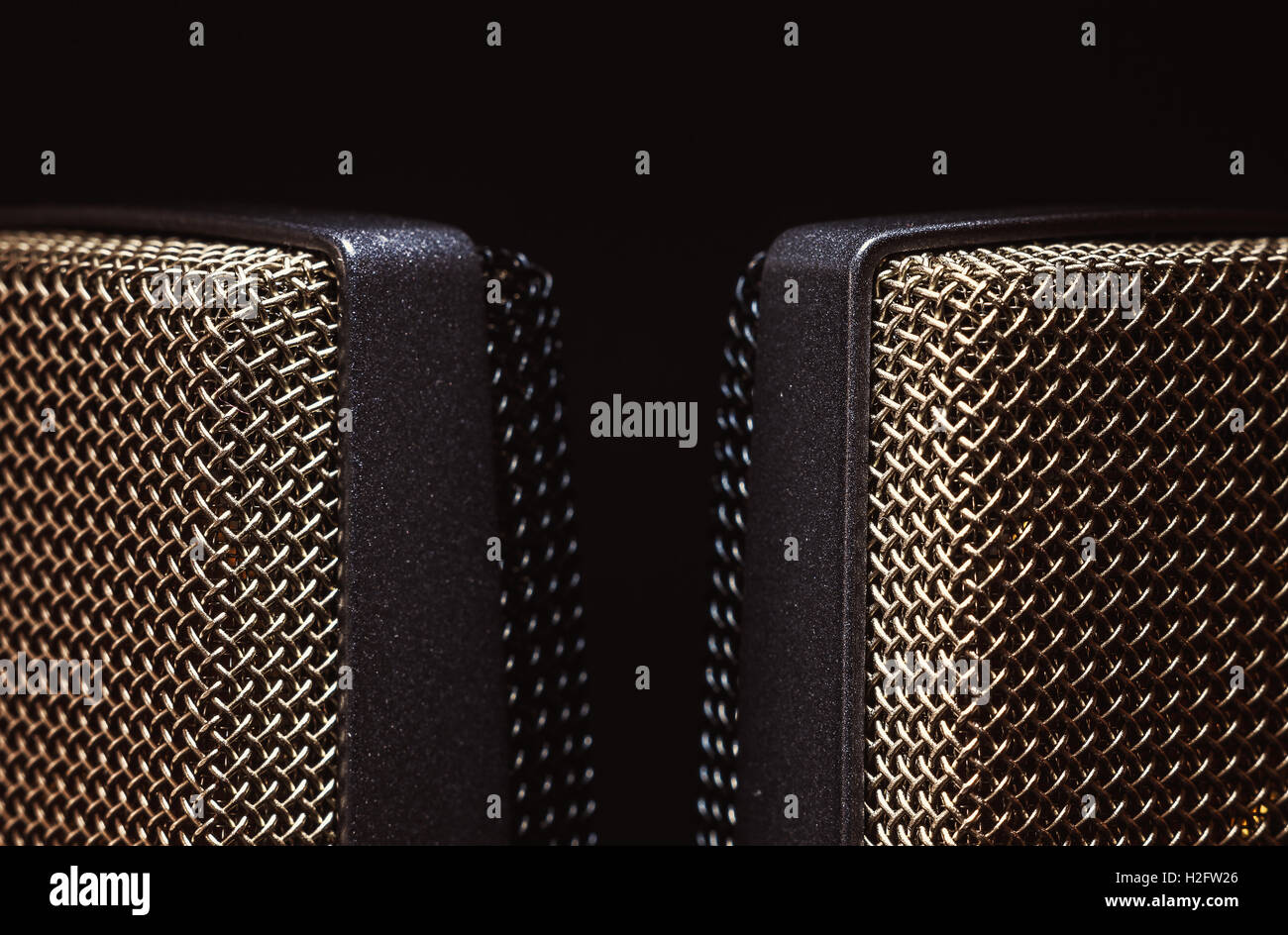 Details of two studio microphones, on black background. - Stock Image