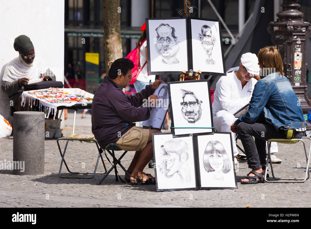 Street artists outside The Pompidou Centre in the Beauborg area near Les Halles, Paris, draw portraits and caricatures - Stock Image