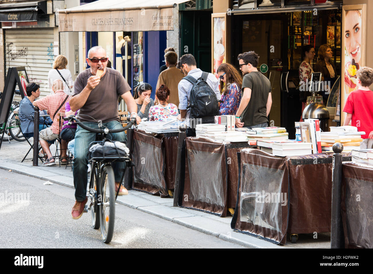 A cyclist eats ice cream as he rides past booksellers in a street in Saint-Germain-des-Prés, - Stock Image