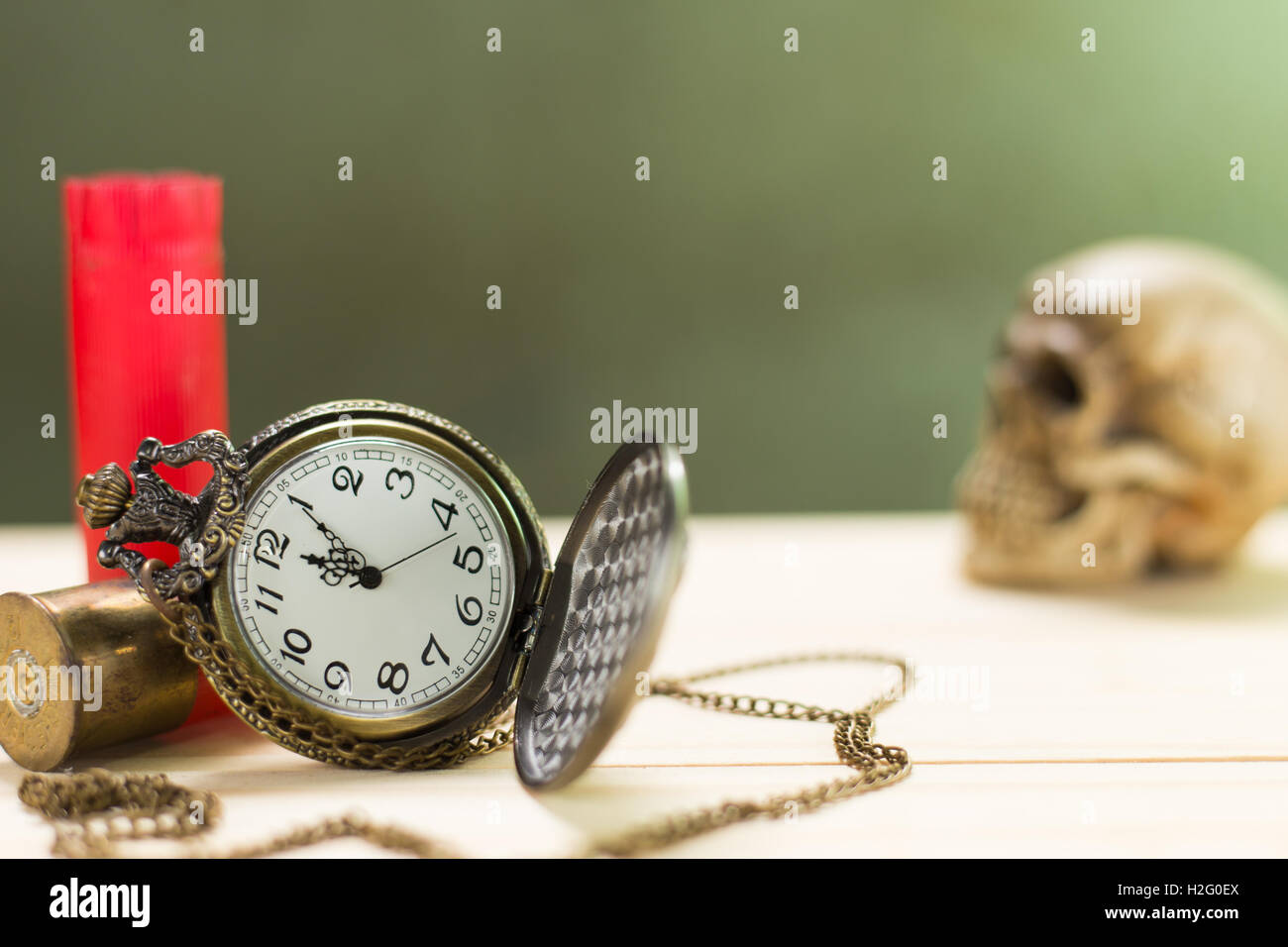 Still life antique clock placed on a wooden floor and a red shotgun shell with human skull on the background. - Stock Image
