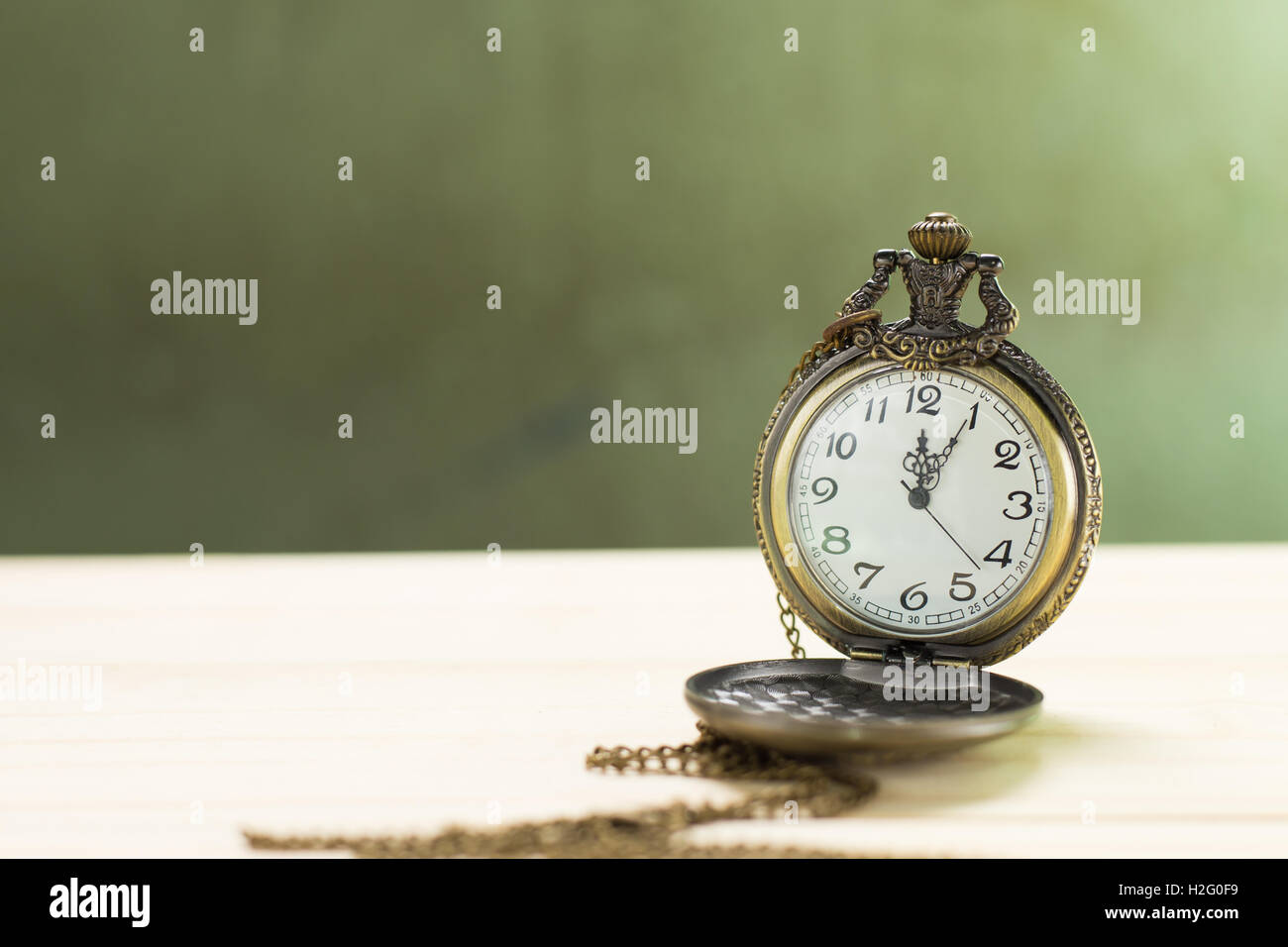 Antique clock on the wooden floor and green wall Background. - Stock Image