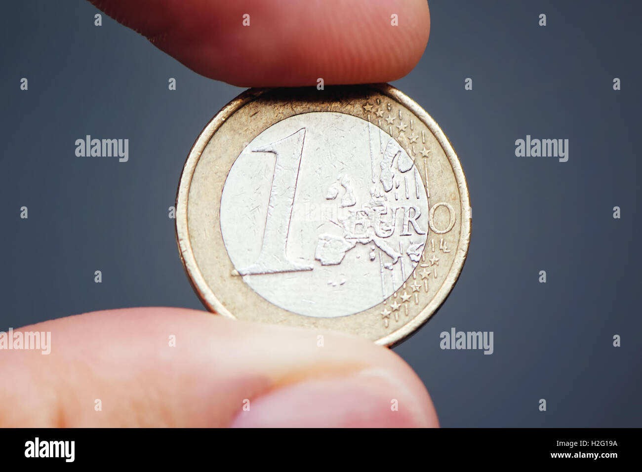 Businessman holding one euro coin between fingers, close up with selective focus - Stock Image