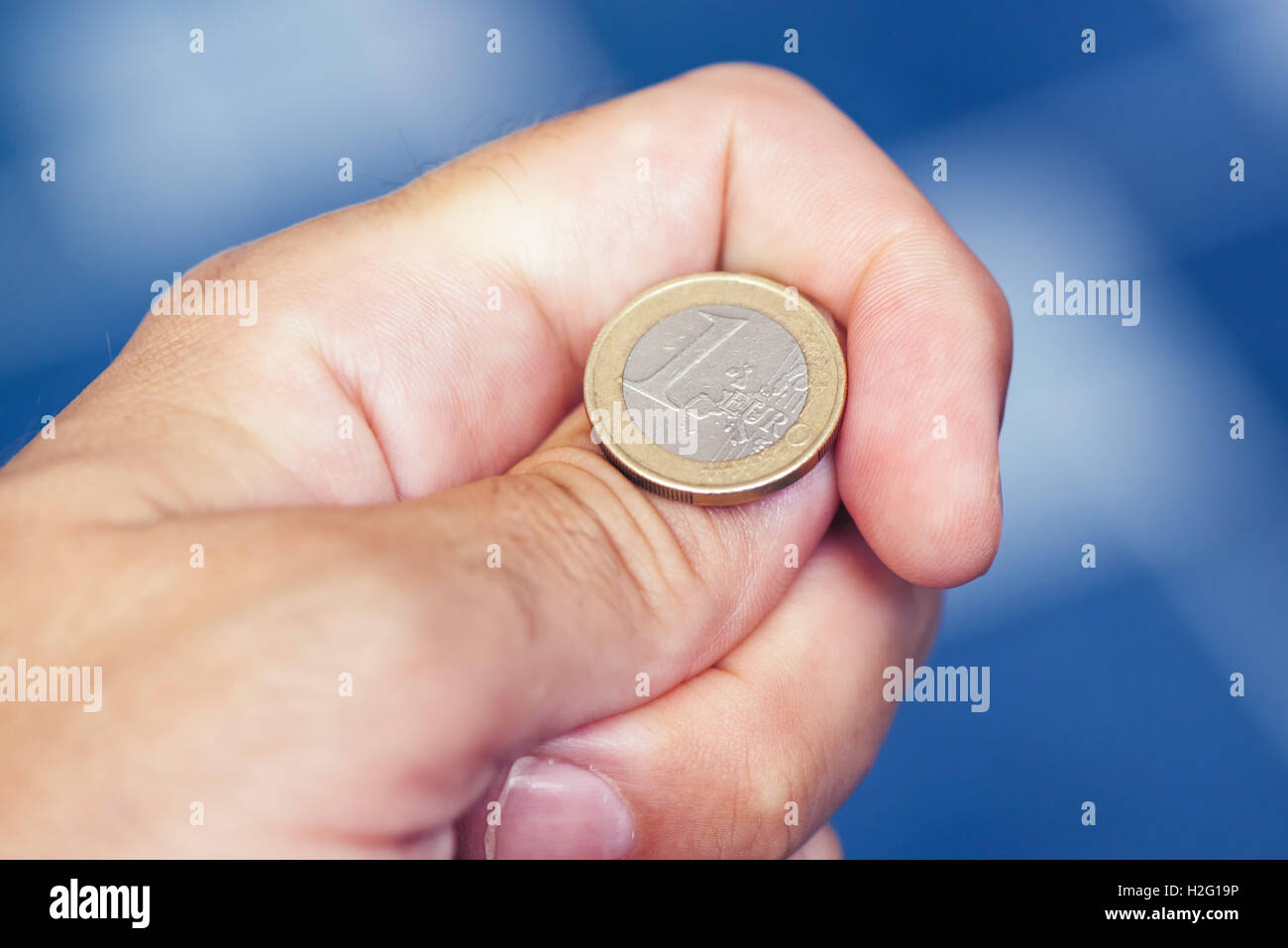 Businessman hand tossing coin to flip on heads or tails, concept of chance, opportunity and decision making - Stock Image
