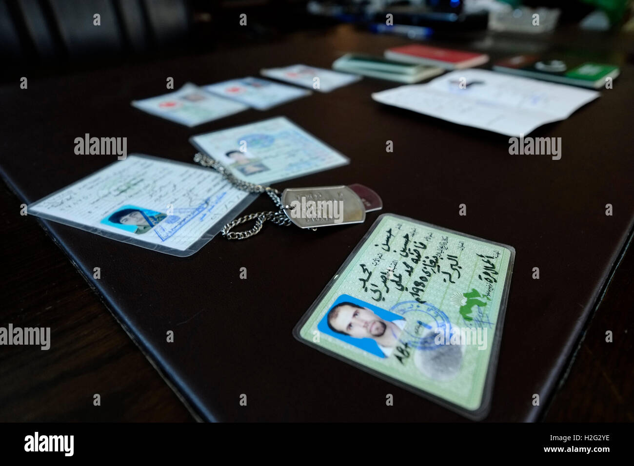 Identity cards and diverse passports of fighters of Islamic State of Iraq and the Levant ISIS or Daesh captured - Stock Image