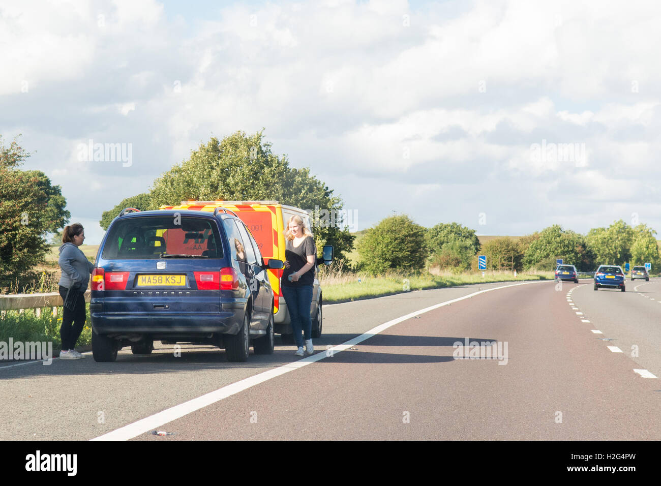 Two young women and car broken down on the A1(M) motorway with AA van - Stock Image