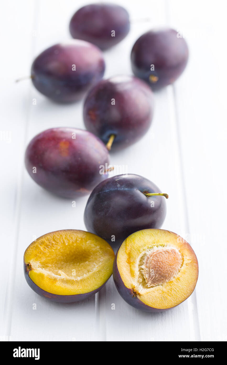 Halved ripe plum on white table. Stock Photo