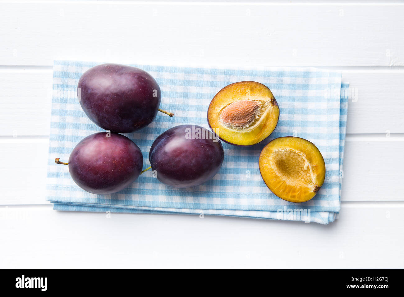 Halved ripe plums on kitchen table. Top view. - Stock Image