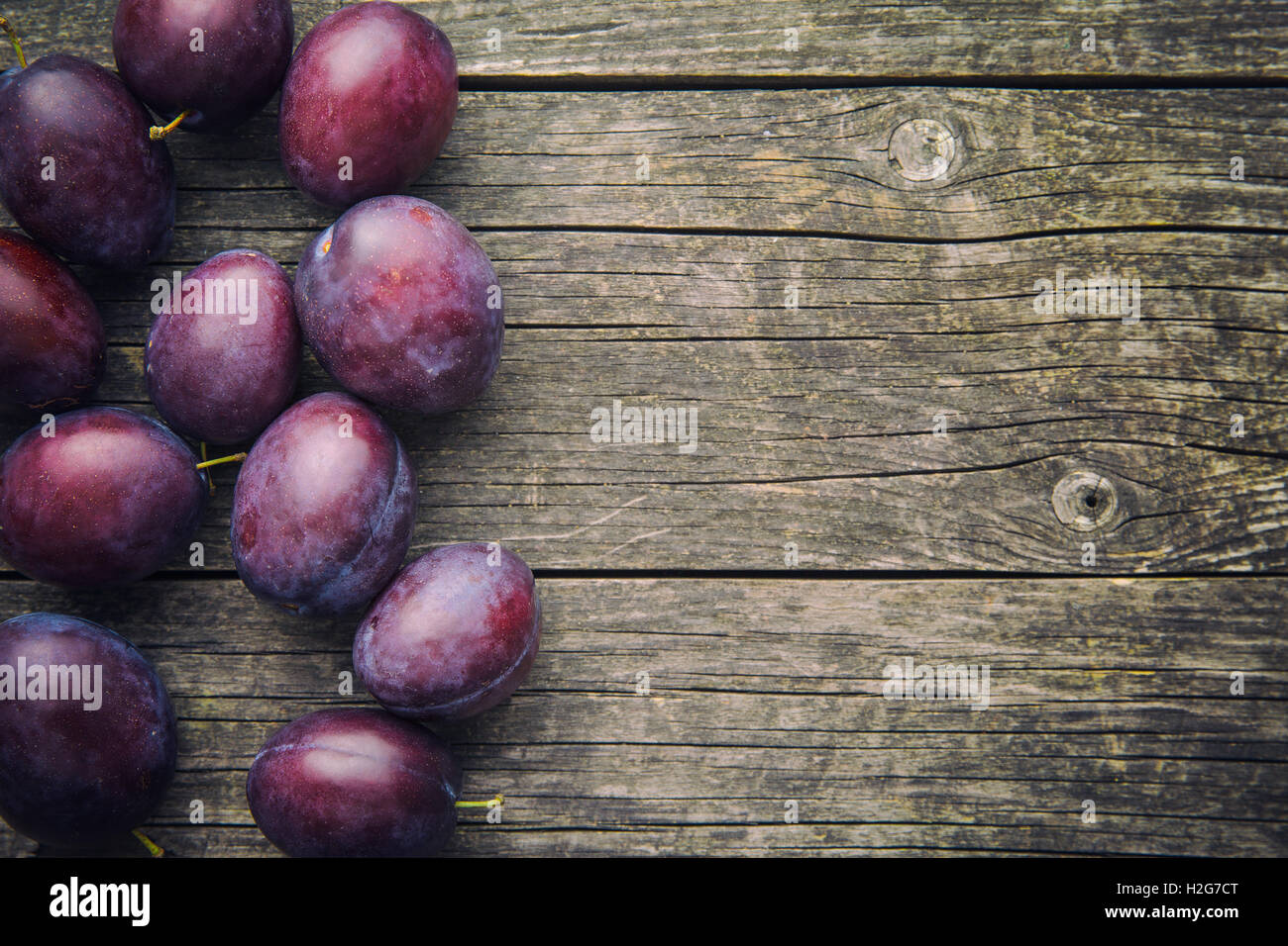 Fresh ripe plums on old wooden table. Top view. - Stock Image