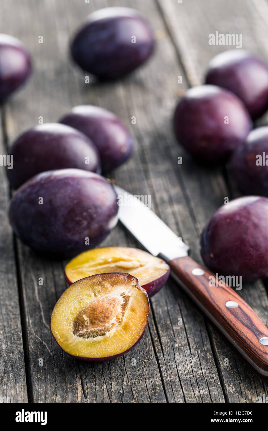 Halved ripe plums and knife on old wooden table. - Stock Image