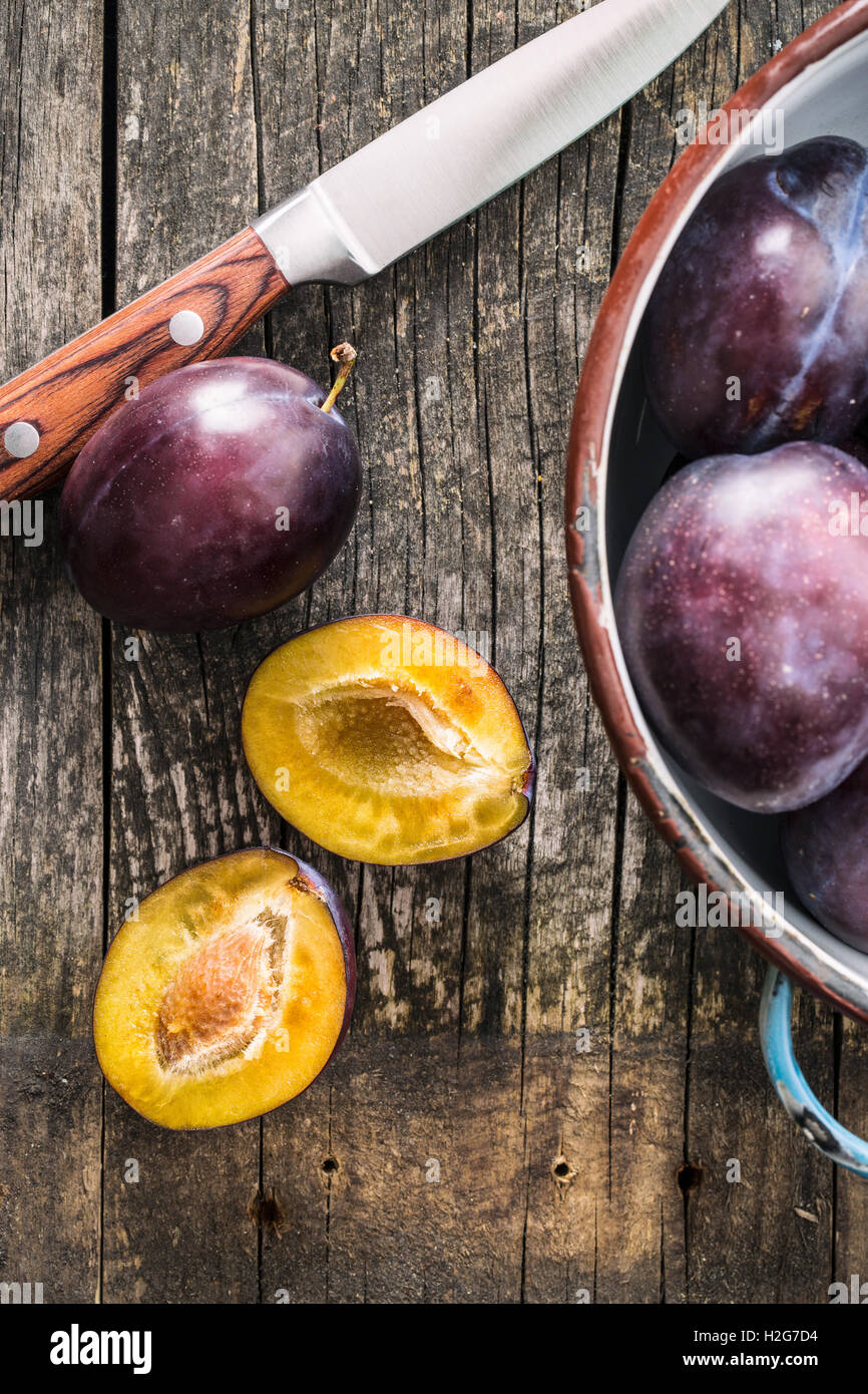 Halved ripe plums and knife on old wooden table. Top view. Stock Photo