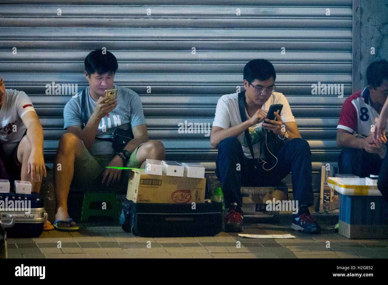 scalpers sell new iPhone 7s outside the Apple Store on Canton Road in Hong Kong to wealthy buyers who don't want Stock Photo