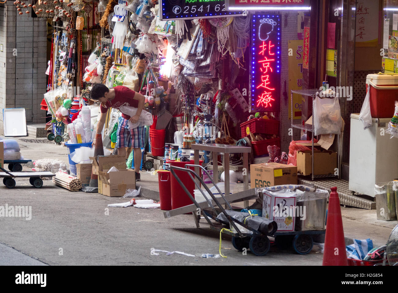 a woman unpacks products for her shop in Hong Kong - Stock Image