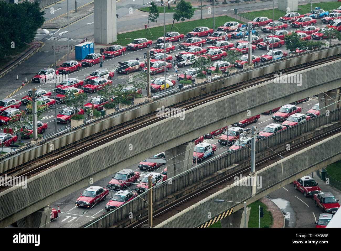 taxis wait to enter the arrivals stand at Hong Kong International Airport - Stock Image