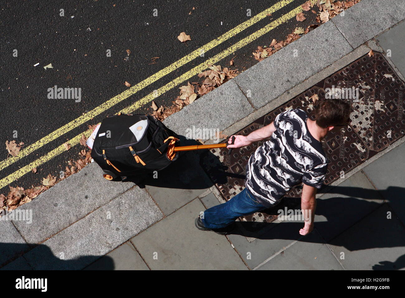 Looking down on a male pulling a wheeled suitcase along a pavement in London, England. Stock Photo