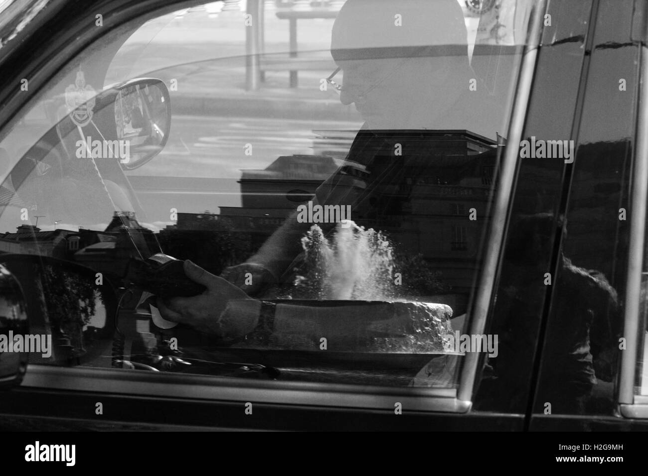 A London Taxi driver taking a card payment in Trafalgar Square - a reflection of one of the fountains in the door Stock Photo