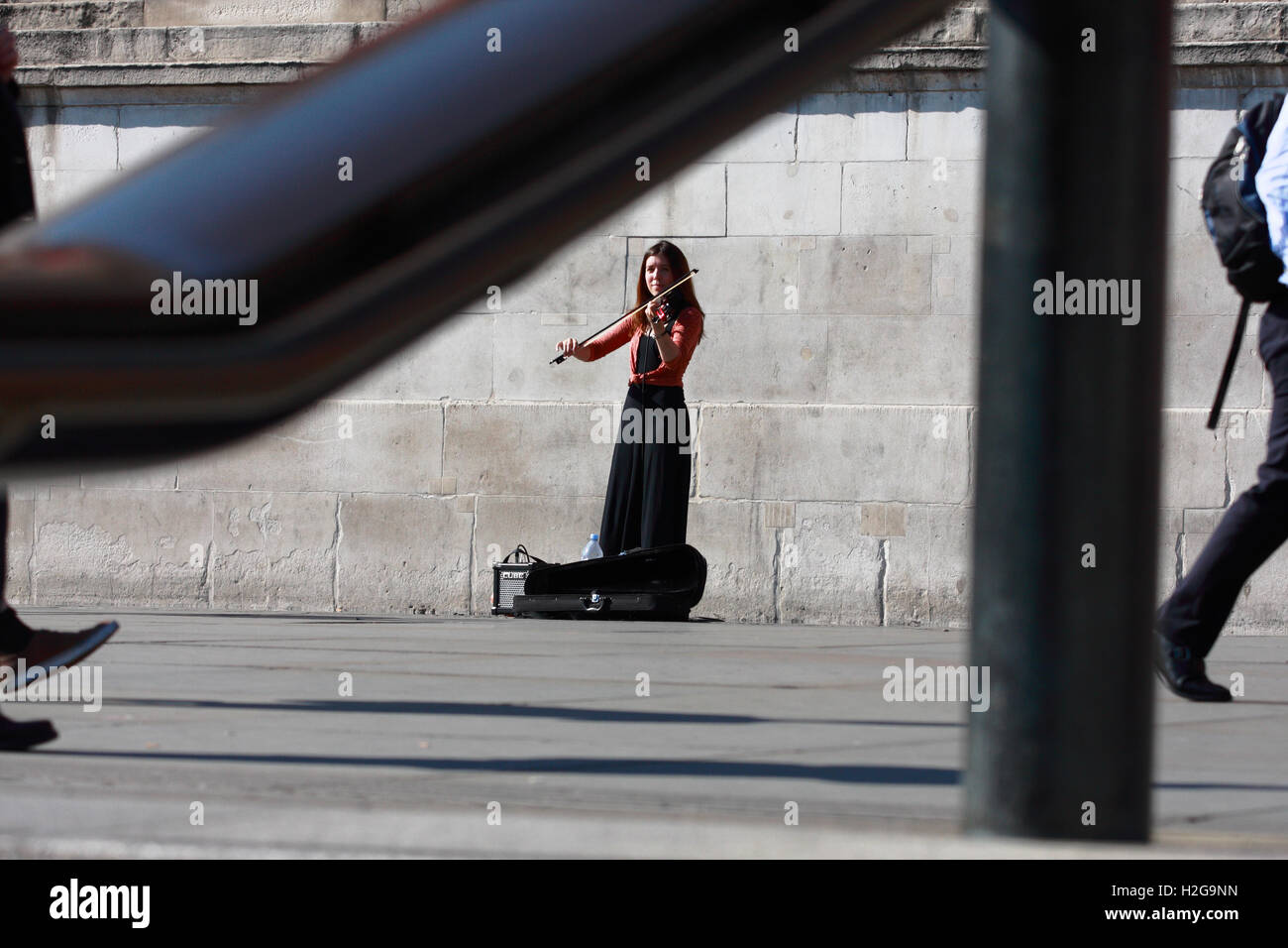 A street entertainer plays her violin in Trafalgar Square, London, England while people walk passed. Stock Photo