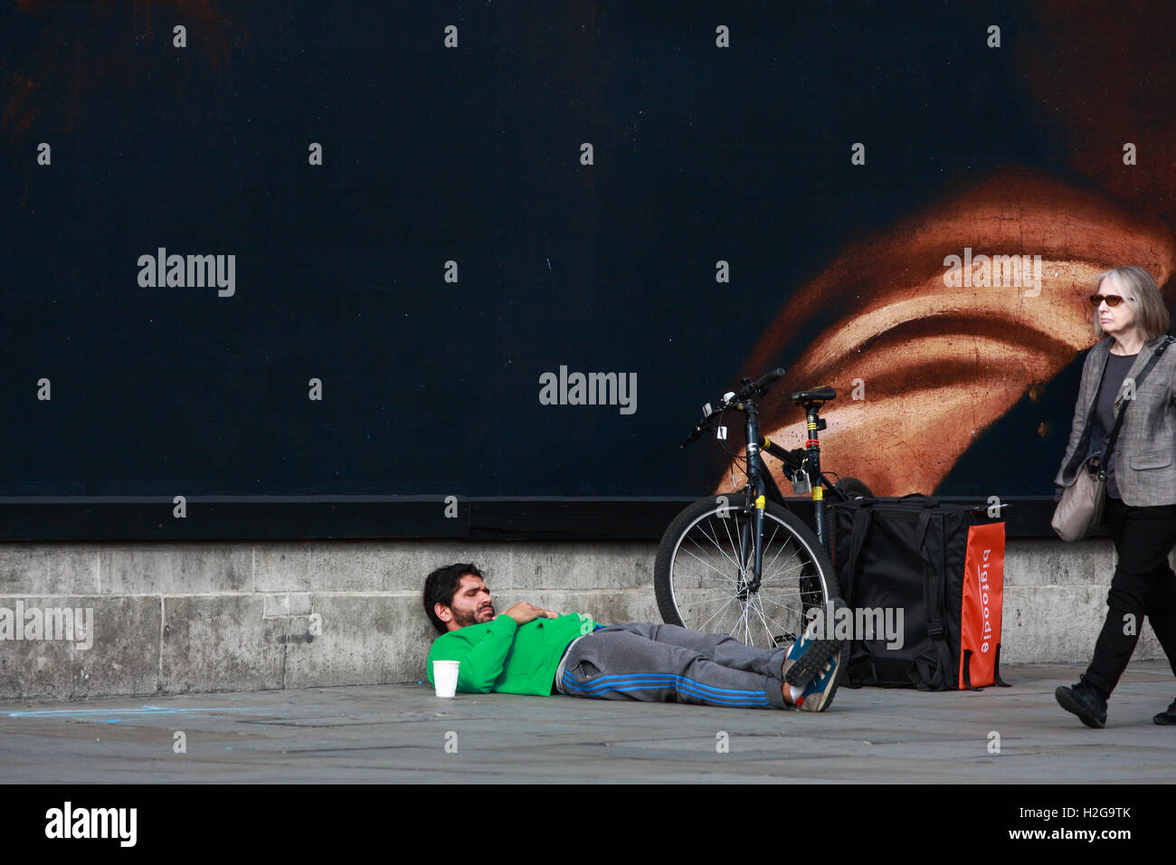 A male lies on the ground, relaxing in Trafalgar Square, London, England and a female walks passed Stock Photo
