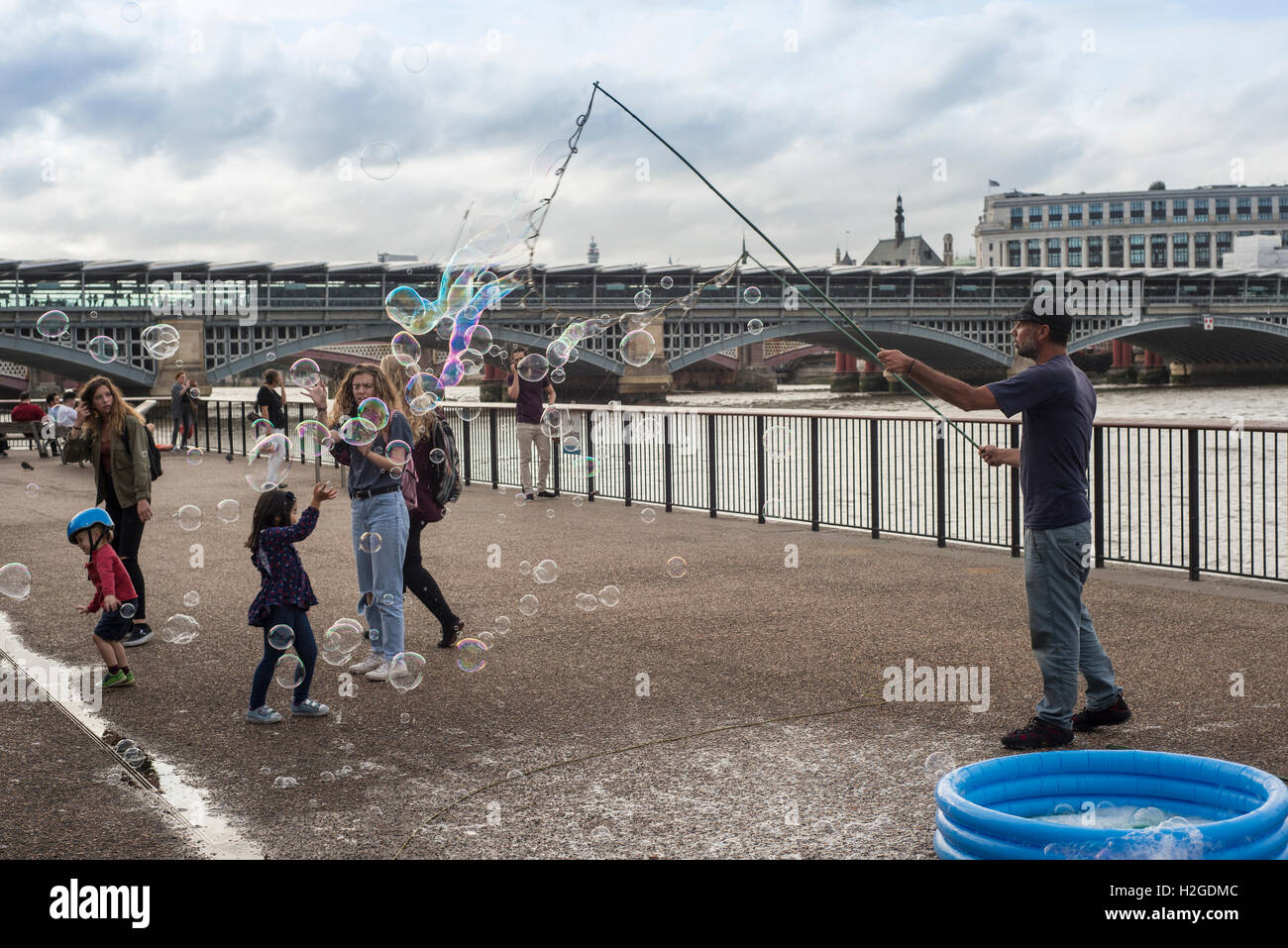 Street entertainer on London's Southbank blowing bubbles for children - Stock Image