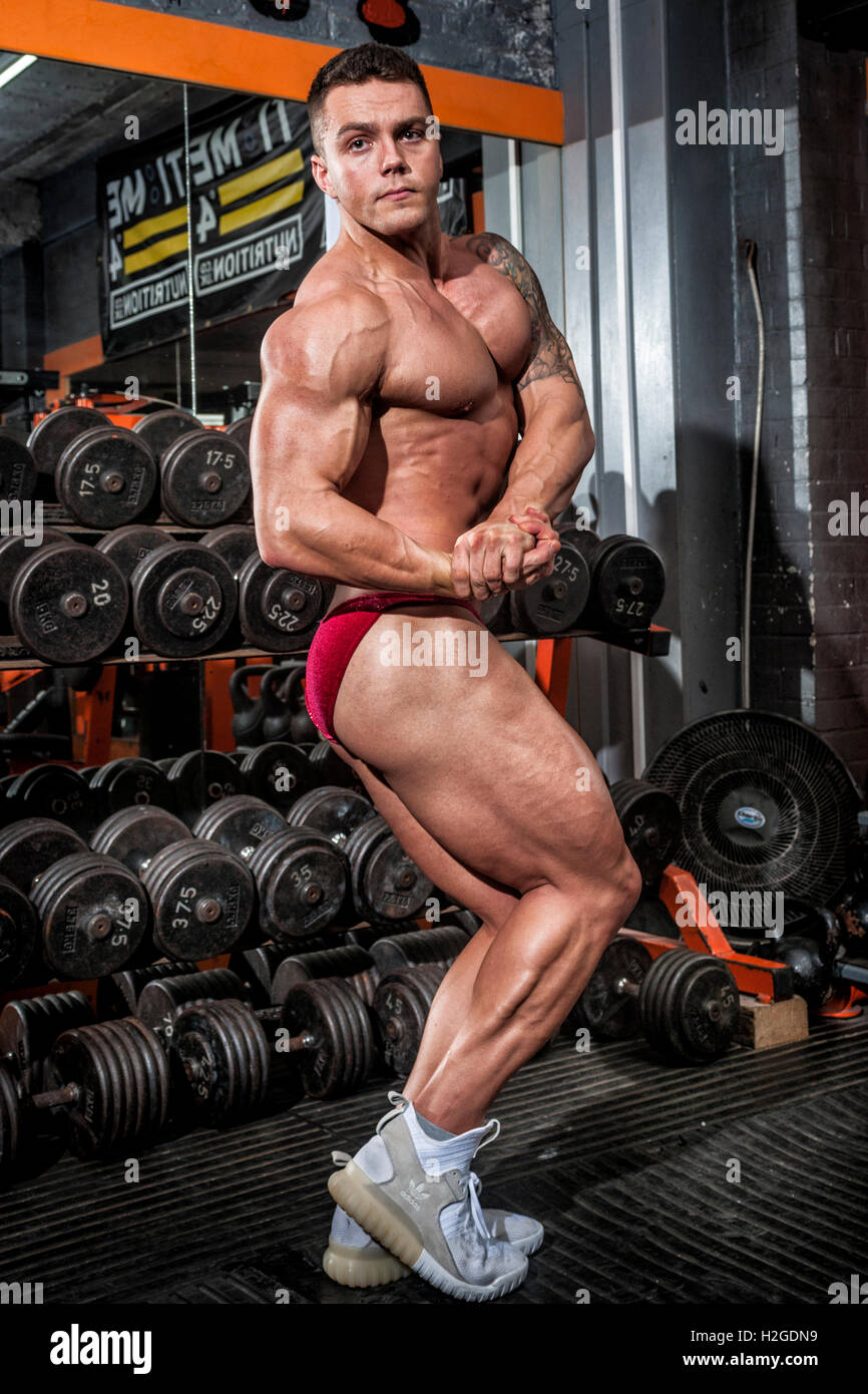 bodybuilder doing competition poses showing defined muscles - Stock Image