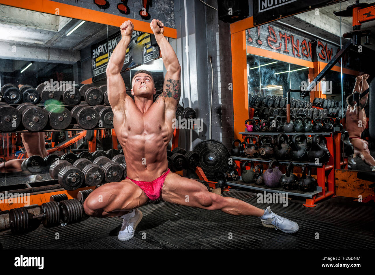 bodybuilder doing competition poses wearing a posing pouch and showing defined muscles - Stock Image