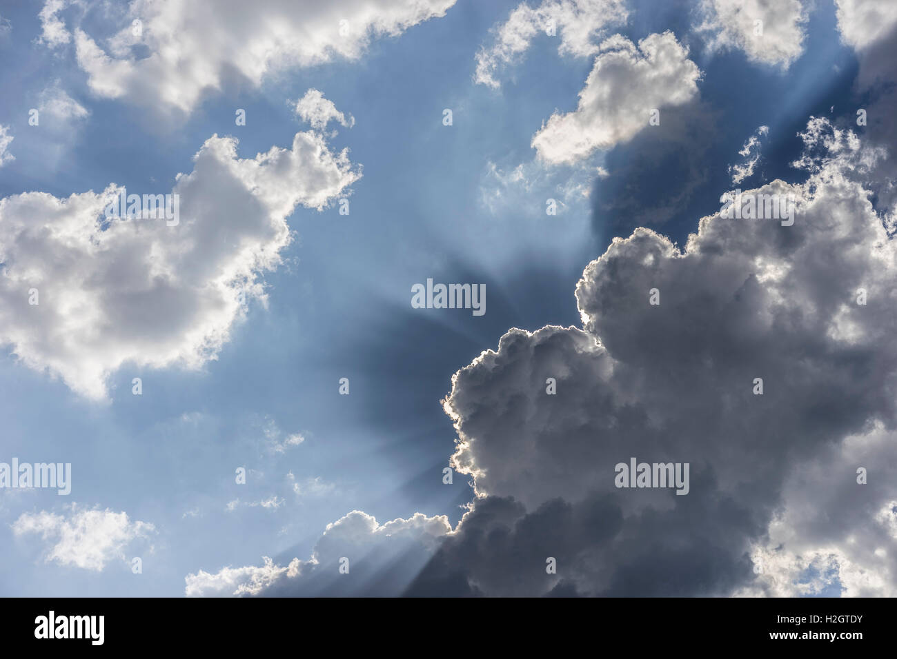 Dark clouds, rain clouds with concealed Sun and sunbeams - Stock Image