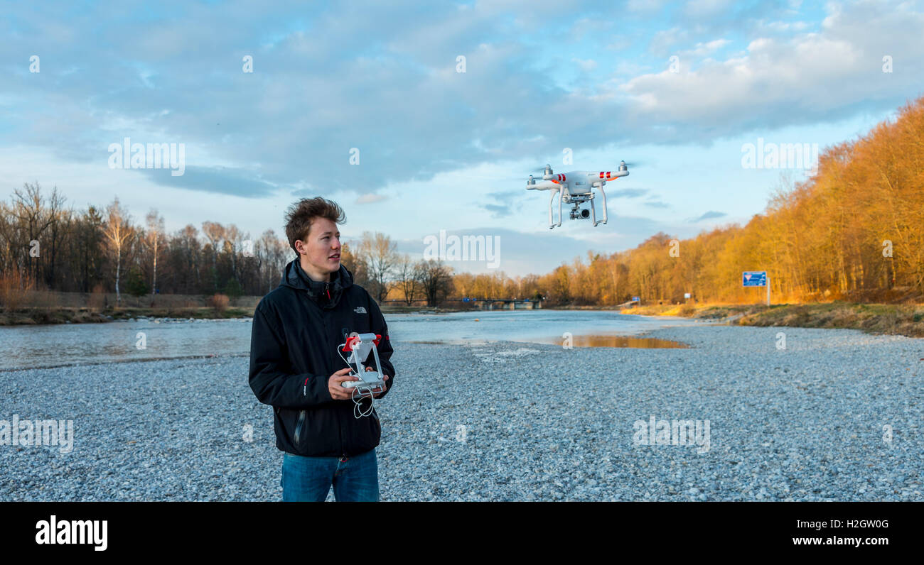 Young man controlling quadcopter, drone with camera flying, DJI Phantom 3, Munich, Upper Bavaria, Bavaria, Germany - Stock Image
