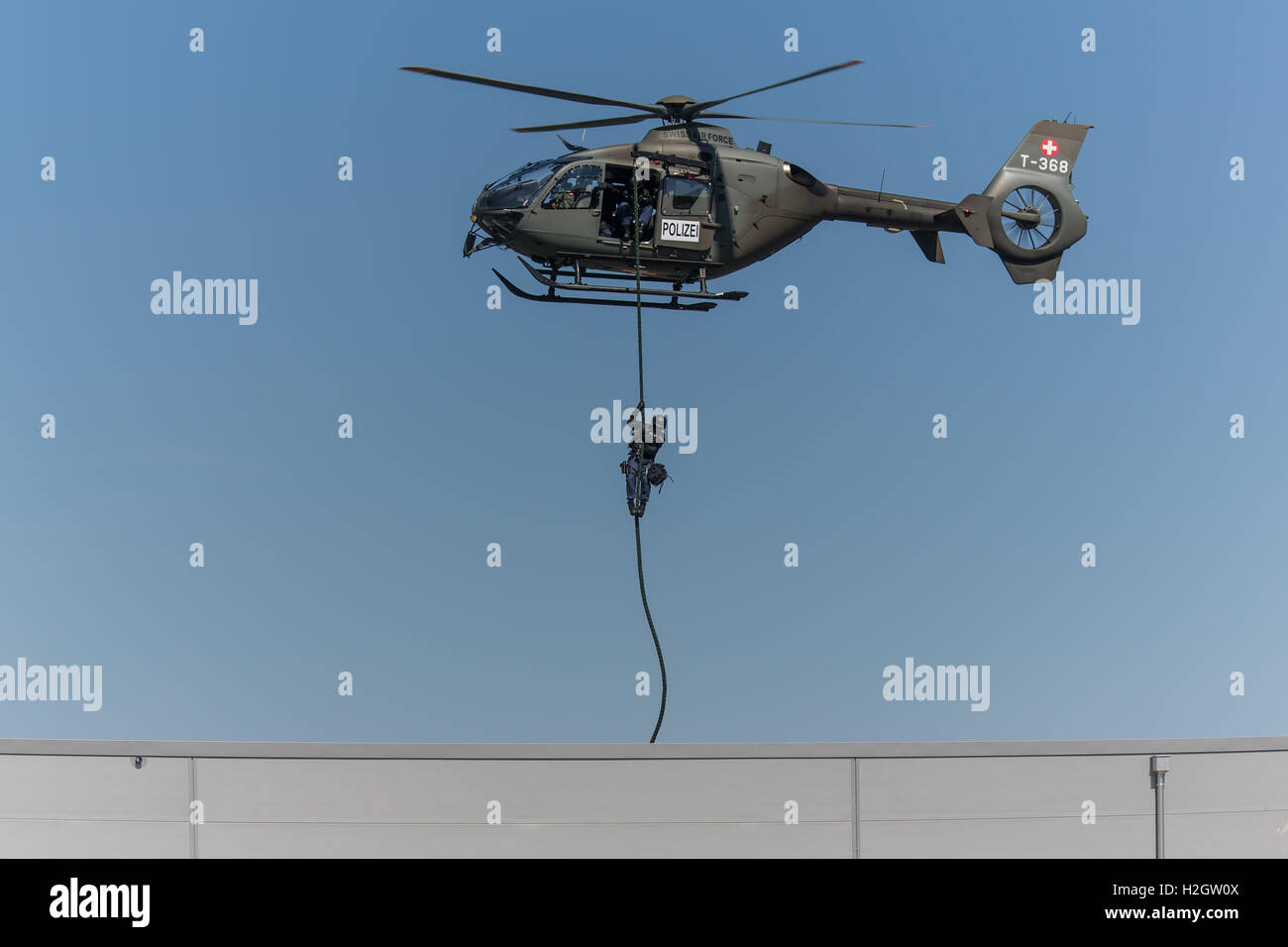 Armed policeman abseiling from helicopter onto roof, body armour, Lucerne police, Luchs special operations group - Stock Image