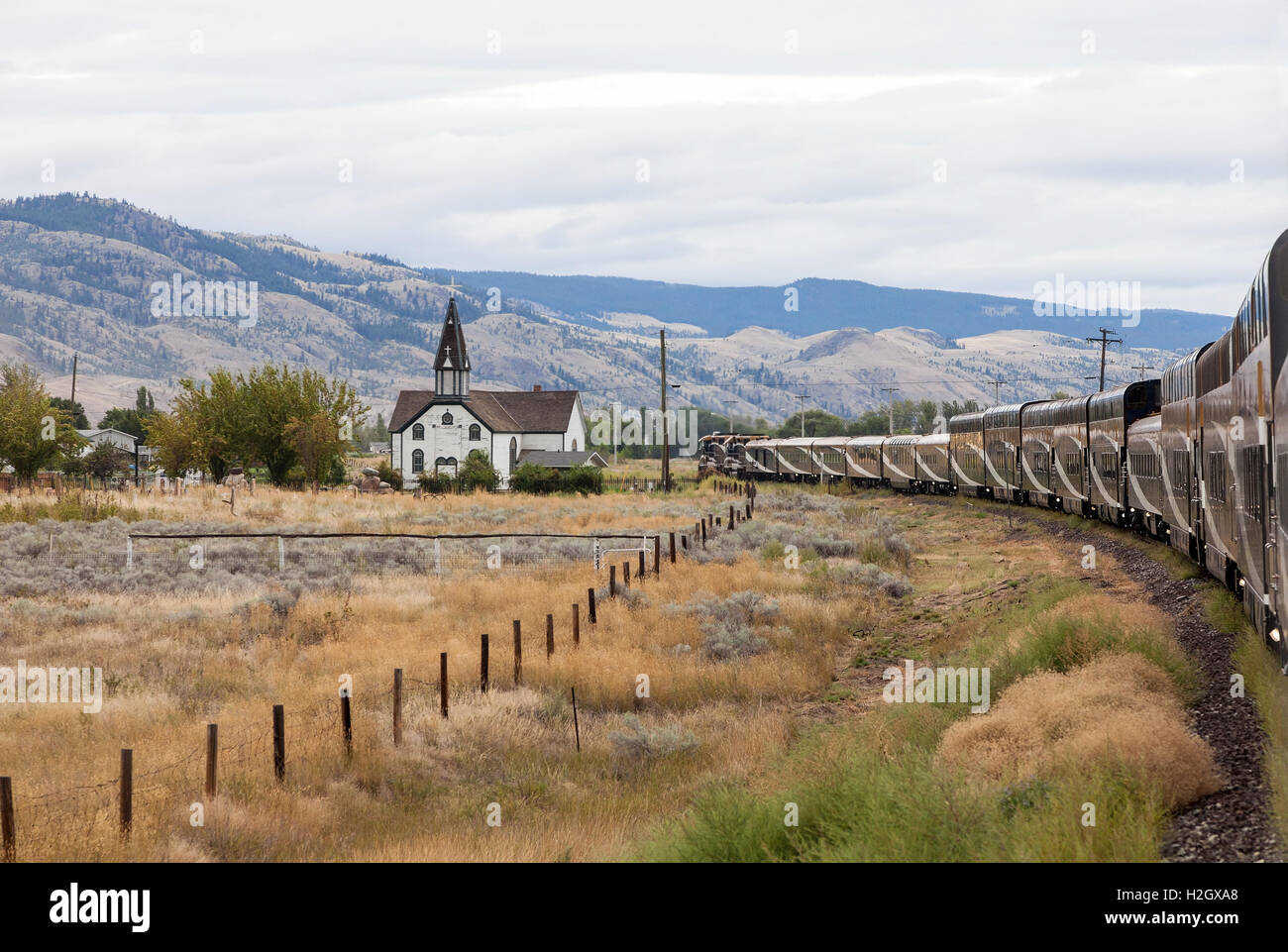 Rocky Mountaineer train passing St. Joseph's Church, a historic small wooden church near Kamloops, Canada - Stock Image