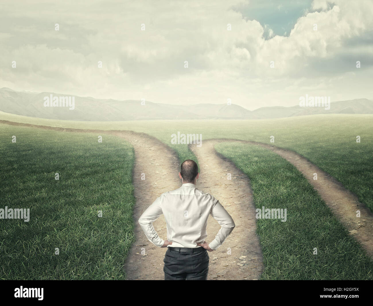 businessman look at crossroad in country road - Stock Image