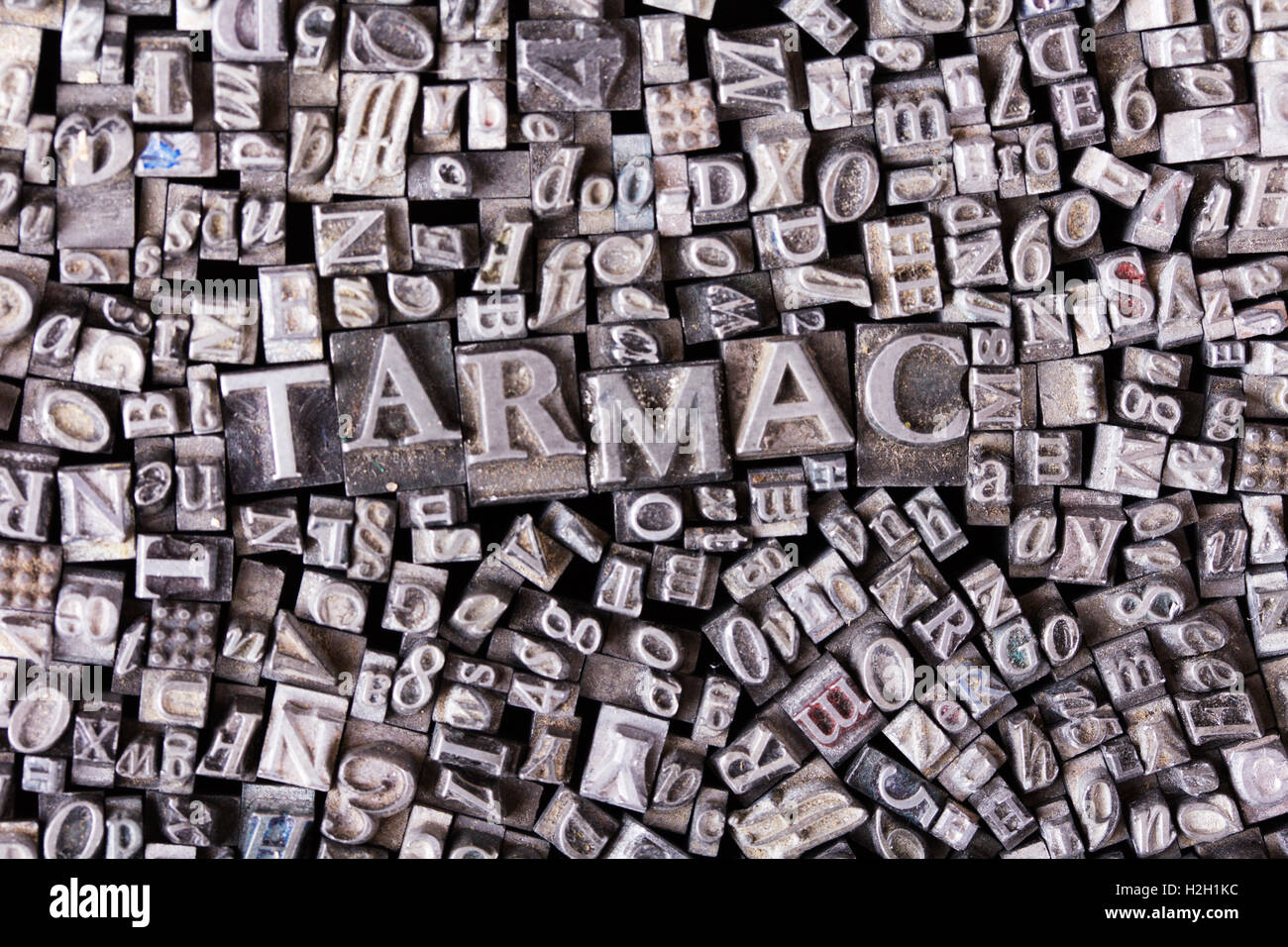 Close up of old used metal typeset letters with the word tarmac - Stock Image