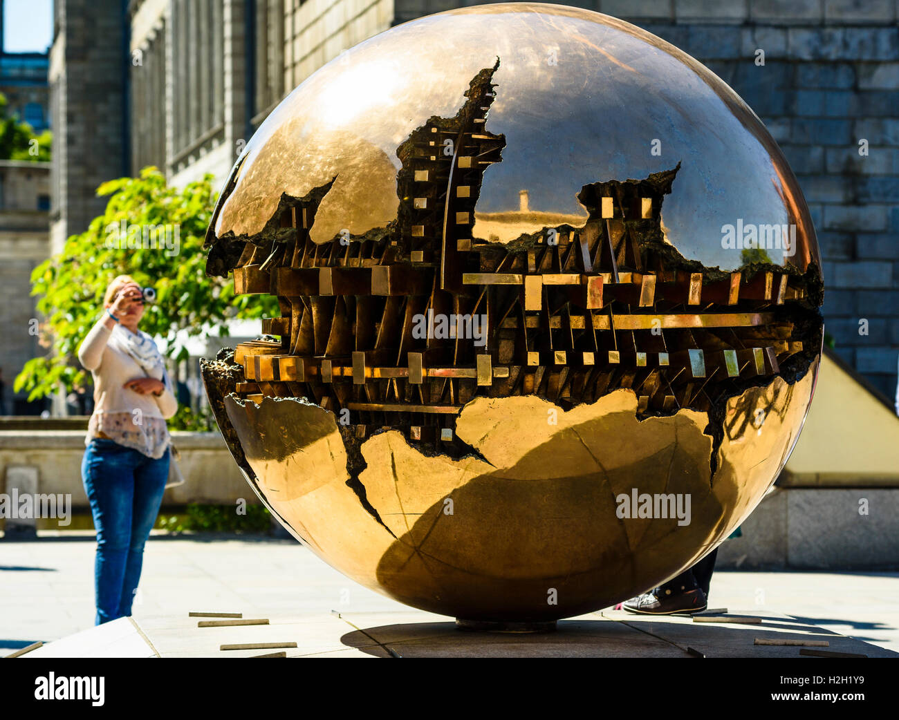 Photographing Sphere Within Sphere (Sfera con sfera) sculpture by Arnaldo Pomodoro, Trinity College Dublin, Ireland - Stock Image