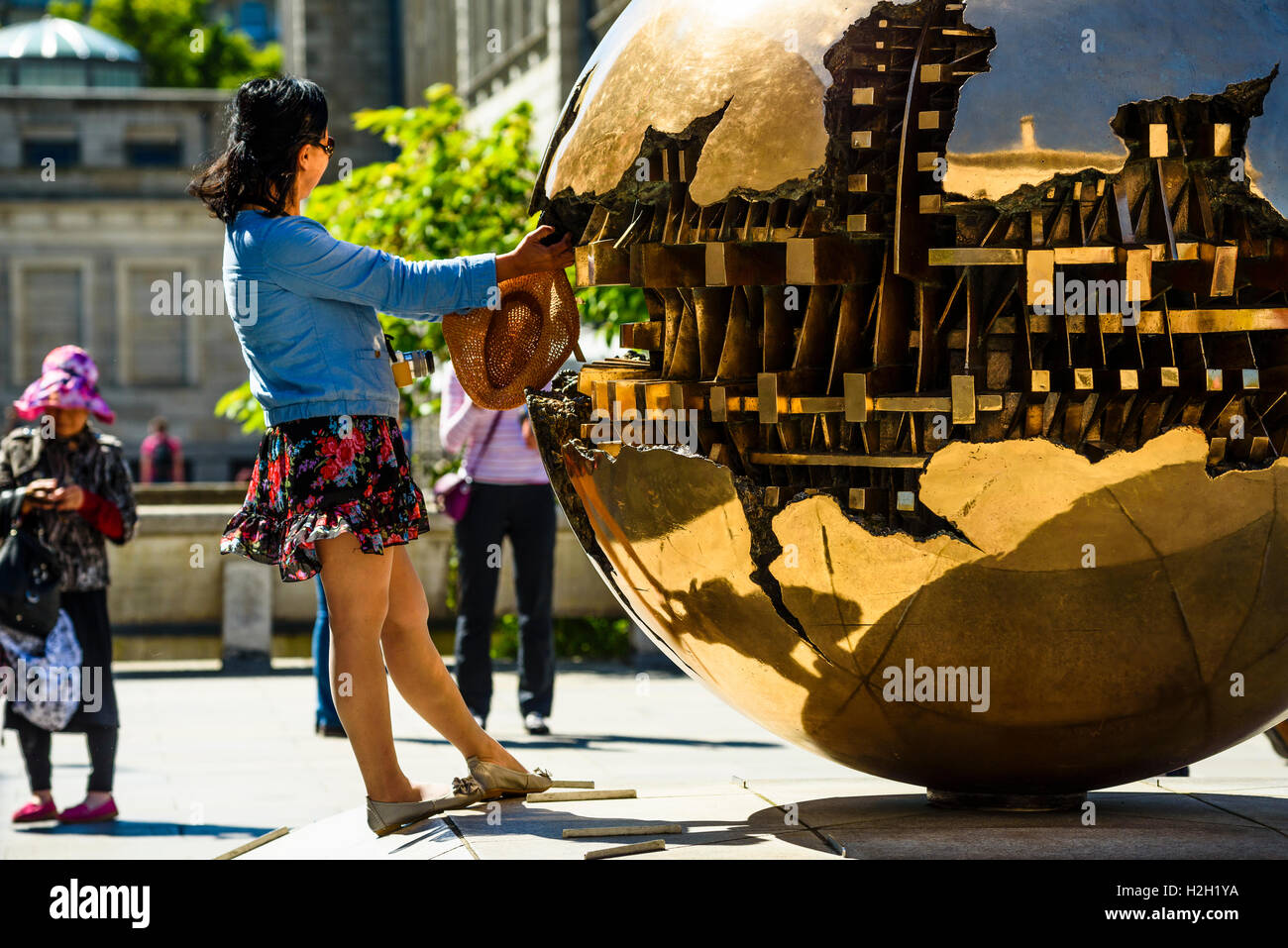 Visitors enjoy Sphere Within Sphere (Sfera con sfera) sculpture by Arnaldo Pomodoro, Trinity College Dublin, Ireland - Stock Image